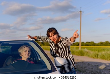 Woman giving directions to a lost woman driver on a rural road pointing in the direction she should drive