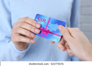 Woman giving gift card to friend, closeup. Holiday celebration concept.