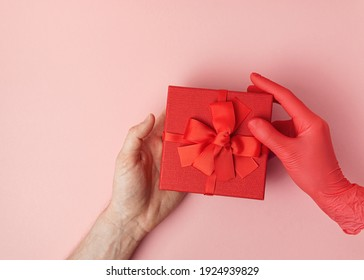 Woman giving a gift in a red box with bow to a man with one hand. The female in red glove. Men's hand without glove.
