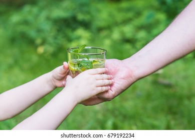 Woman giving a glass of clean water to a child. Green background.