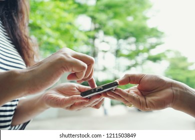 Woman giving handwritten signature with a smartphone or digital signing for goods received from delivery man, blurred background of building and green zone of trees. (selective focus, space for text)