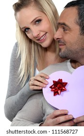 a woman giving a heart shaped box to her husband