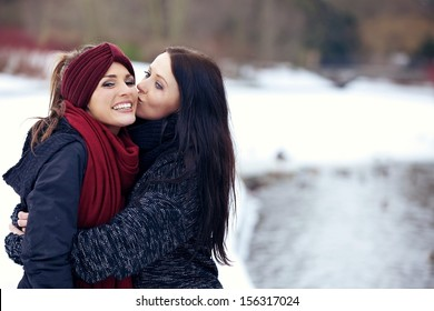 Woman giving her friend a friendly kiss on the cheek outdoors