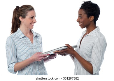 Woman giving laptop to her friend