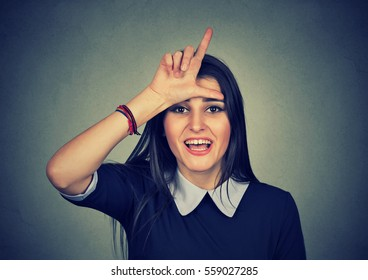 woman giving loser sign looking at you, making fun isolated on gray wall background