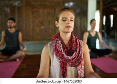 Woman giving meditation course to two multi-ethnic men on yoga mats in traditional temple in Bali Indonesia
