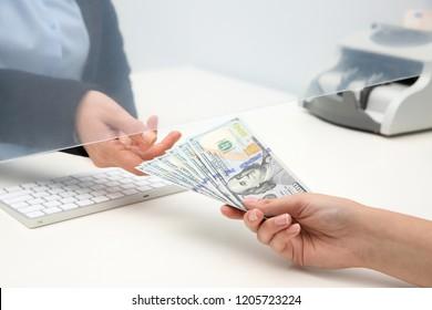 Woman giving money to teller at cash department window, closeup