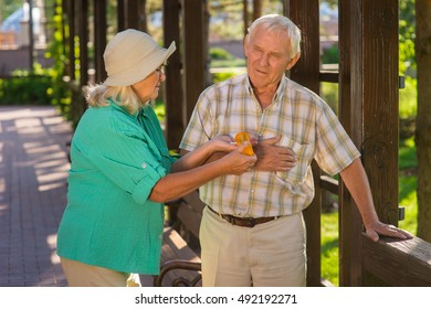 Woman giving pills to man. Senior male has heart ache. You forgot to take medicine. Wife takes care of husband.