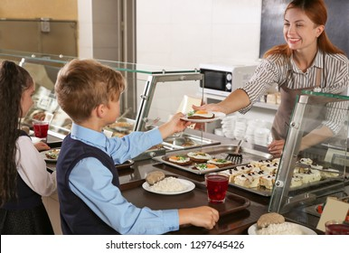 Woman giving plate with healthy food to boy in school canteen