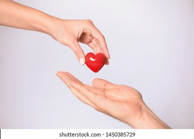 Woman giving red heart to man on white background, closeup. Donation concept