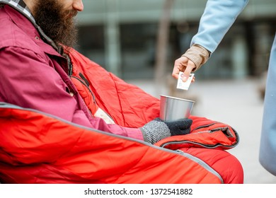 Woman giving some money for a homeless beggar, close-up view. Concept of help and charity