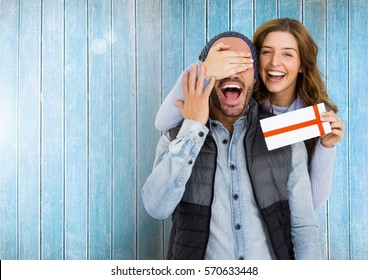 Woman giving surprise gift to man against wooden background