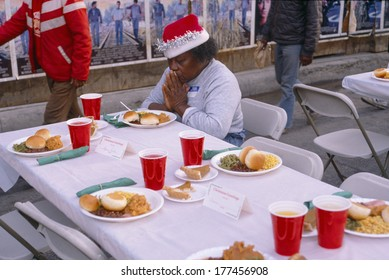 A woman giving thanks for her Christmas dinner, Los Angeles Mission, CA