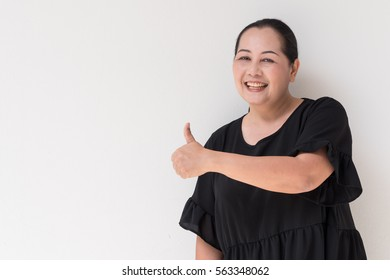 woman giving thumb up to her side, middle age asian model
