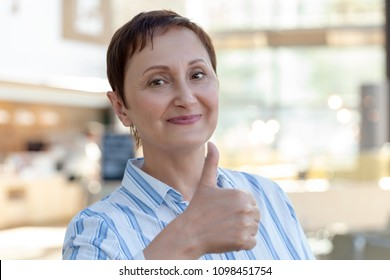 Woman giving  thumbs up, the thumb sign of approval. Middle aged older woman portrait. Blurred office store cafe background
