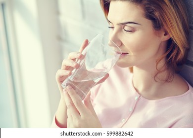 Woman with a glass of clean drinking water