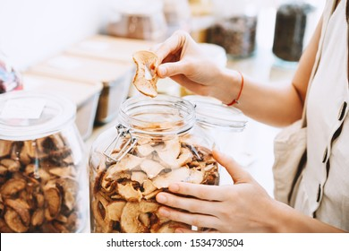 Woman with glass jars buying dried berries and fruits in zero waste shop. Sustainable shopping in plastic free grocery store. Minimalist lifestyle of vegan young girl with white reusable cotton bag