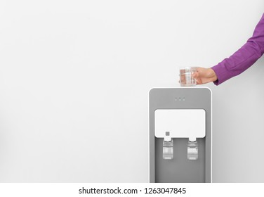 Woman with glass near water cooler on white background, closeup. Space for text