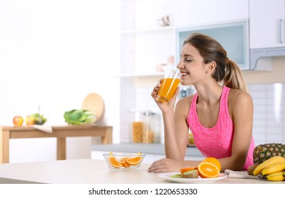 Woman with glass of orange juice at table in kitchen. Healthy diet