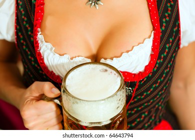 Woman with glass or stein of beer in front of her decollete, she is wearing Bavarian Tracht, a Dirndl