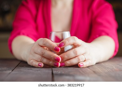 Woman with glass of whiskey on wooden table