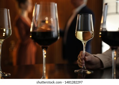 Woman with glass of wine in restaurant, closeup