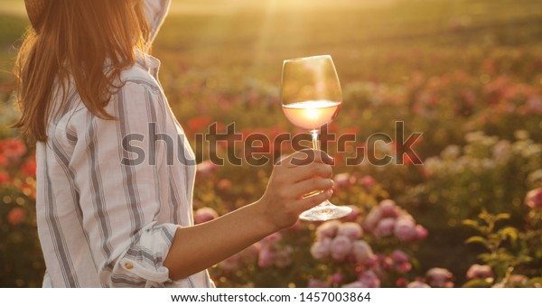 Woman with glass of wine in rose garden on sunny day, closeup. Space for text