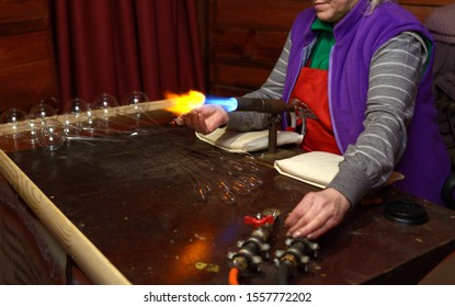 Woman glassblower warming glass blank with a gas burner, another hand opening the valve supplying gas to the gas burner. November 1, 2019. Kiev, Ukraine