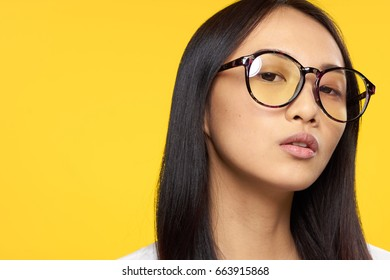 Woman in glasses, woman background, woman on yellow background portrait.