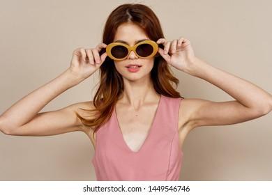 woman in glasses - beautiful portrait on a beige background