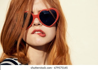 Woman in glasses bites her lip on a light background portrait