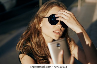 A woman with glasses fixes her hair and looks into the phone