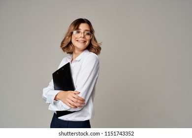 a woman in glasses hugs a black folder with documents