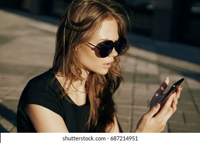 Woman with glasses looks at the phone on the street.