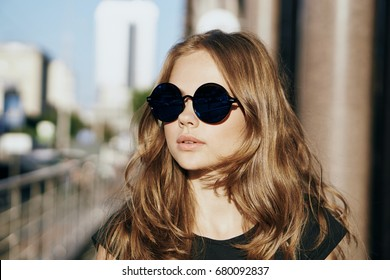 Woman in glasses on building background, street