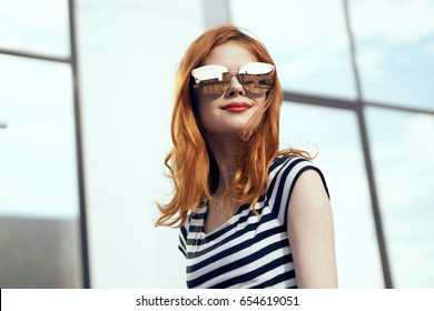 Woman in glasses, woman on mirror building background