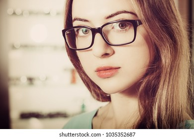 woman with glasses in the optical salon standing and looking to the camera