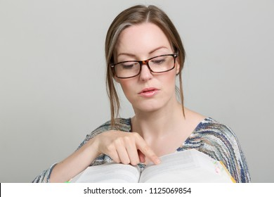woman with glasses is reading in a book