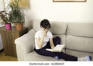 Woman with glasses reading a book on a sofa next to some green plants