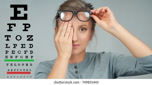Woman in glasses reviewing eyesight closing eye with hand. Eye test. Eyesight vision exam chart