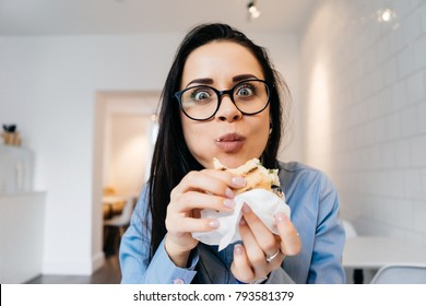 a woman in glasses sits in the office and eats a sandwich