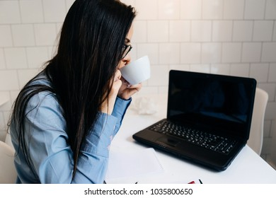 woman in glasses sits at table in office and drinks coffee