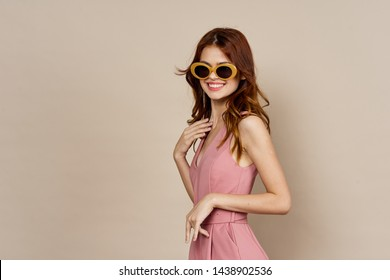 woman in glasses smiling on a beige background