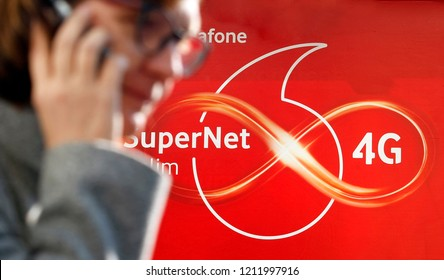 A woman in glasses speaks on a phone next to a logo SuperNet 4G of Vodafone mobile operator, in Kiev, Ukraine, on 18 October 2018.