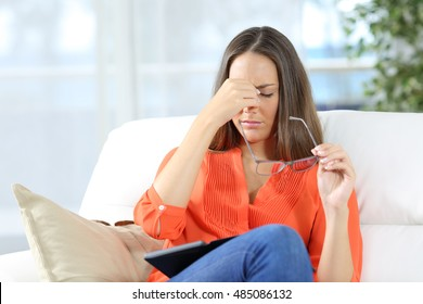 Woman with glasses suffering eyestrain after reading an ebook sitting on a couch at home