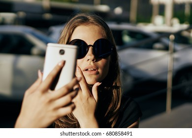 A woman in glasses takes pictures of herself