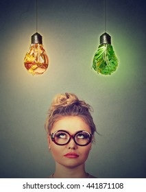 Woman in glasses thinking looking up at junk food and green vegetables shaped as light bulb above head isolated on gray wall background. Diet choice right nutrition healthy lifestyle concept