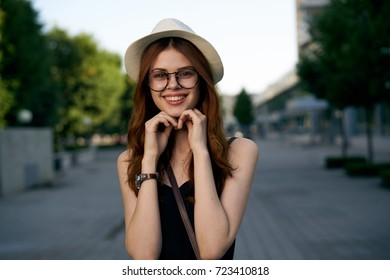 woman in glasses and wearing a hat smiling on the road in the city, portrait.