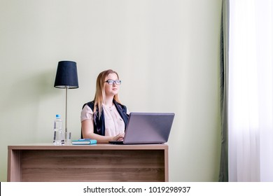Woman with glasses working at laptop sitting in office