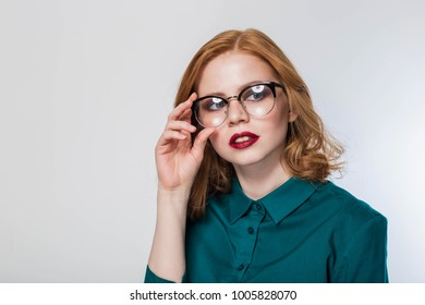 woman in glasses,woman on a white background. Beautiful redhead business woman with the green shirt